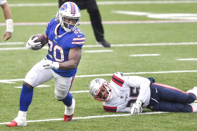 Buffalo Bill Zack Moss (20) rushes past the New England Patriots' Terrence Brooks during the first half of Sunday's game in Orchard Park, New York.