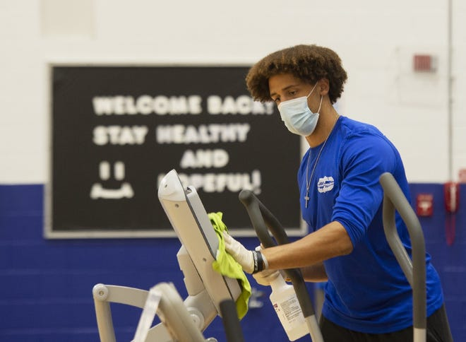 Tyler Barney, fitness activities coordinator at the Twinsburg Fitness Center, sanitizes equipment in the facility during the summer. Twinsburg city employees can now pay the residential rate at the fitness center under a measure recently approved by city council.