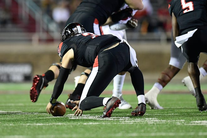 Texas Tech's Henry Colombi (4) dives after a fumbled snap during a Big 12 Conference game Saturday against Oklahoma at Jones AT&T Stadium.
