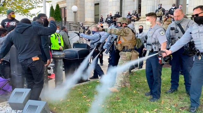 Alamance County sheriff's deputies use pepper spray on a crowd of protesters outside the courthouse in Graham, N.C., on Saturday. A get-out-the vote rally that ended with North Carolina police pepper spraying and arresting attendants was the result of participants blocking the roadway without authorization, authorities said. (Carli Brosseau/The News & Observer via AP)