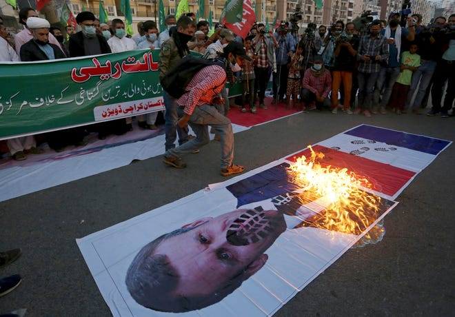 Pakistani Shiite Muslims burn a representation of a French flag and a defaced image of French President Emmanuel Macron during a rally Sunday against the French president and the republishing of caricatures of the Prophet Muhammad they deem blasphemous, near the French consulate in Karachi, Pakistan.