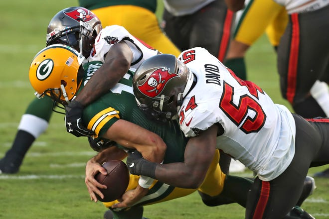 Tampa Bay Buccaneers inside linebacker Lavonte David (54) and outside linebacker Jason Pierre-Paul (90) team up to sack Green Bay Packers quarterback Aaron Rodgers (12) during the second half of an NFL football game Oct. 18 in Tampa.