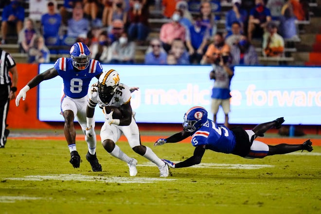 Florida linebacker Khris Bogle (8) and defensive back Kaiir Elam (5) come in on Missouri running back Larry Rountree III in the first half Saturday at Ben Hill Griffin Stadium.