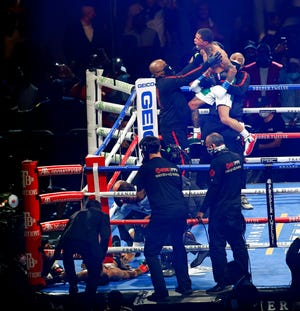 Gervonta Davis, top center, celebrates with his corner after knocking out Leo Santa Cruz, lower left, in the sixth round of a WBA super featherweight and WBA lightweight boxing bout Saturday in San Antonio.