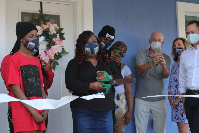 Sylvia Lowery, center, with scissors, and three of her children take part in a dedication ceremony for a home built by Habitat for Humanity of Palm Beach County. Palm Beach Gardens residents Dale and Barbara Dorinski, at right, sponsored the West Palm Beach home to mark their 50th wedding anniversary.