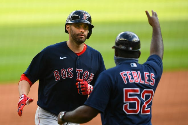 Boston's J.D. Martinez, left, is congratulated by third base coach Carlos Febles as he runs bases during a two-run home run during a game last season.
