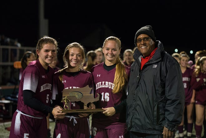 Millbury captains Abigail Gilbert, Amanda Sarro and Audra McDuffie join their coach Hussein Issa to hold up the Division 3 Central title last November.