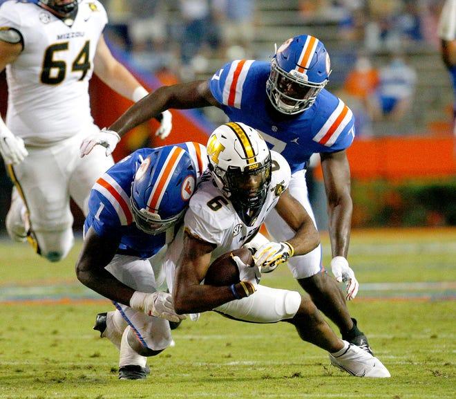 Florida linebacker Brandon Cox Jr. (1) tackles Missouri receiver Jalen Knox during Saturday's game against Missouri at Ben Hill Griffin Stadium.