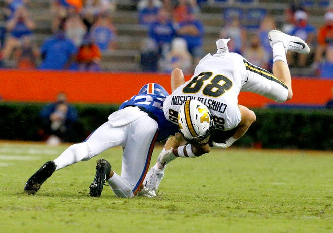 Missouri tight end Logan Christopherson is upended by a Florida defender after making a catch Saturday at Ben Hill Griffin Stadium.