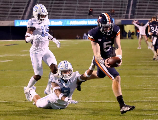 Virginia quarterback Brennan Armstrong, right, reaches for a touchdown as North Carolina defensive backs Cam'Ron Kelly and Ladaeson Hollins, back left, give chase Saturday night at Scott Stadium.