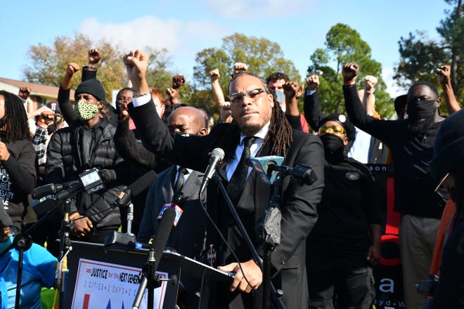 Rev. Gregory Drumwright raises a fist, Sunday, after announcing another get-out-the-vote march scheduled for Tuesday.
