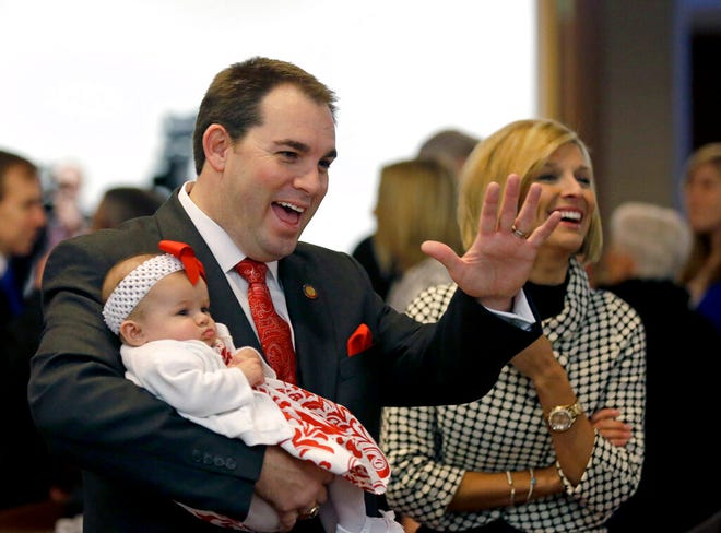 FILE - In this Jan. 14, 2015 file photo, Rep. John Bell, R-Wayne, holds his daughter Averi as he and wife Kelli greet lawmakers during the opening session of the North Carolina Legislature in Raleigh, N.C.   North Carolina General Assembly control in November 2020 likely will come down to outcomes in about 15 closely contested House and Senate races. Democrats need to win six additional House seats and five more Senate seats to ensure majorities in the chambers held by Republicans since 2011.(AP Photo/Gerry Broome, File)