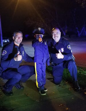 New Philadelphia police auxiliary officers Brian Klopfer (left) and Robert Everett found a protégé Saturday evening on the Southside of New Philadelphia. The boy attracted their attention because he was operating a battery-powered car with red and blue flashing lights on the back. The auxiliary officers distributed candy from a cruiser on Halloween.
