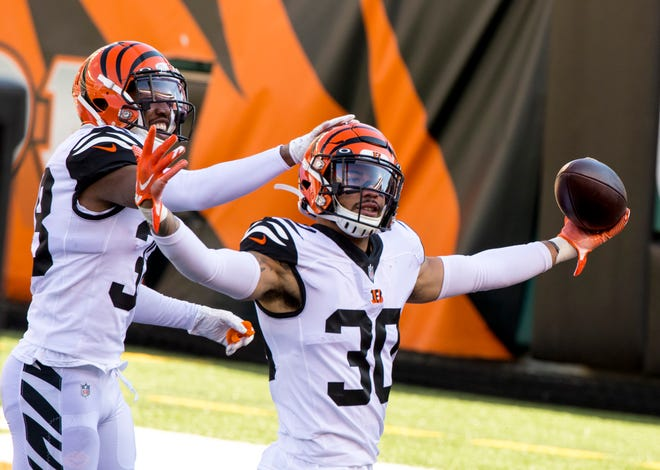 Cincinnati Bengals free safety Jessie Bates (30) celebrates with Cincinnati Bengals cornerback LeShaun Sims (38) after intercepting a pass in the end zone for a touchback in the first quarter of the NFL game between Cincinnati Bengals and Tennessee Titans on Sunday, Nov. 1, 2020, in Cincinnati.