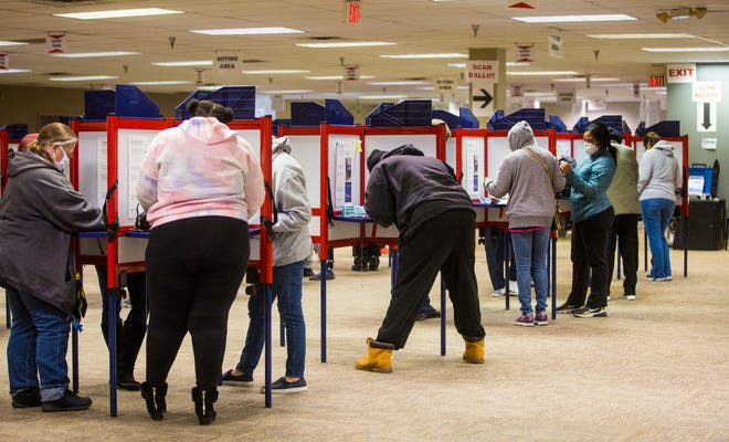 Voters take part in early voting at the Hamilton County Board of Elections worker, Sunday, Nov. 1, 2020. Workers cleaned each station after voting. There were long lines, but the line moved steadily. Nov. 3, is Election Day. Masks are required to vote.