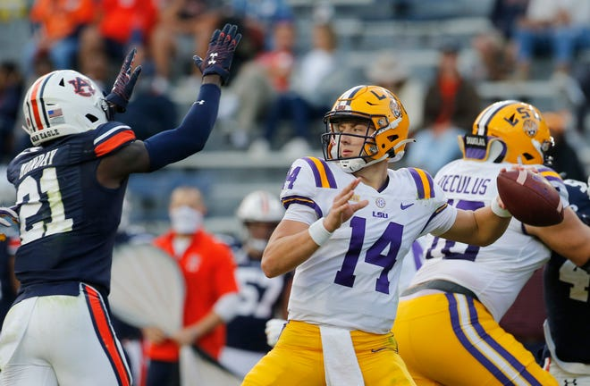 Oct 31, 2020; Auburn, Alabama, USA;  LSU Tigers quarterback Max Johnson (14) is pressured by Auburn Tigers defensive back Smoke Monday (21) during the third quarter at Jordan-Hare Stadium. Mandatory Credit: John Reed-USA TODAY Sports
