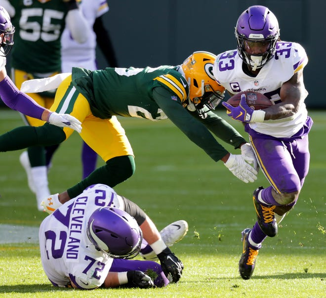 Minnesota Vikings running back Dalvin Cook (33) scores a touchdown on a 50-yard reception while eluding Green Bay Packers free safety Darnell Savage (26) during the third quarter of their game Sunday, November 1, 2020 at Lambeau Field in Green Bay, Wis.