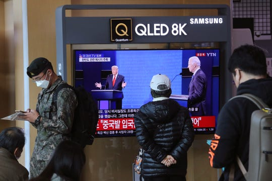 A person in the Seoul Railway Station in Seoul, South Korea, watches a live broadcast of U.S. President Donald Trump and Democratic presidential candidate former Vice President Joe Biden during the final presidential debate.