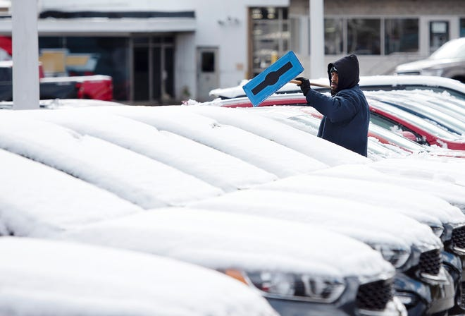 Antwon Edwards clears snow from vehicles at Ron Lewis Ford and Kia Monday morning in Beaver Falls. Despite a chilly coating of snow Monday morning, none is in the forecast for Election Day — though bundle up for temperatures in the low to mid-50s with brisk winds.