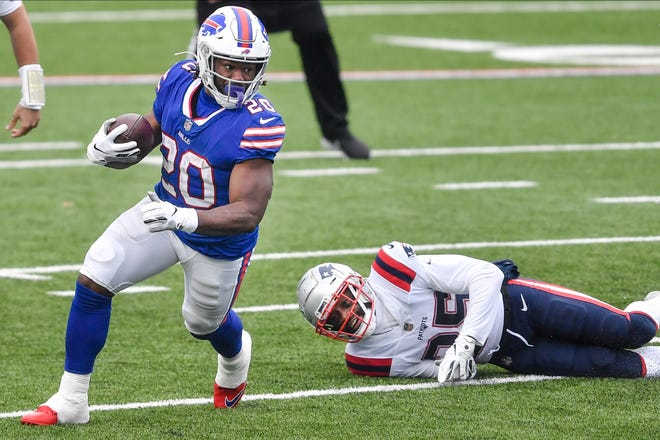 Buffalo's Zack Moss rushes past New England's Terrence Brooks in the Bills' victory Sunday in Orchard Park, N.Y. [Adrian Kraus/Associated Press]