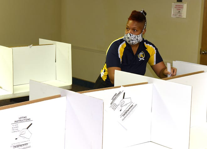 Election Supervisor Monique Fugate sets up voter booths on Monday for precinct 3A at the Church of Nazarene.