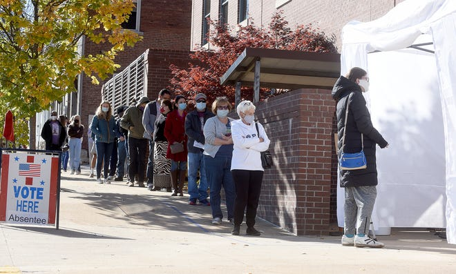 People wait to vote absentee ballots on Monday at the outdoor Boone Government Center. Turnout is expected to shatter records nationwide.