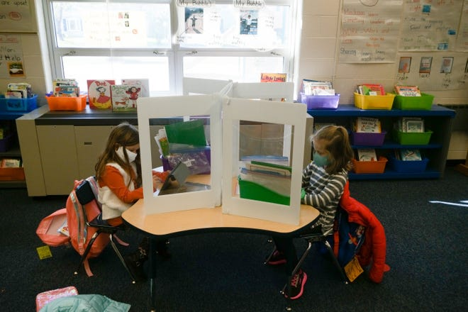 Kindergartners work on a writing exercise while separated with a plastic barrier as part of COVID-19 precautions in classrooms on Monday, Nov. 2, 2020 in Hilliard, Ohio.