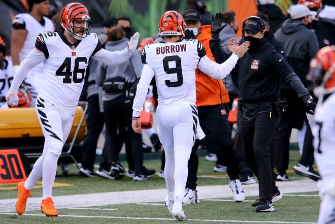 Cincinnati Bengals quarterback Joe Burrow prepares to accept a high-five from coach Zac Taylor after Burrow's touchdown pass to Tyler Boyd in Sunday's win over Tennessee.