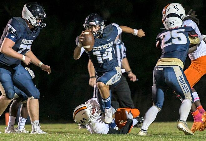 Eustis quarterback Blayne Romano (14) leaps over Leesburg's Mason Burke (44) during Friday's game at the Panther Den in Eustis. [PAUL RYAN / CORRESPONDENT]