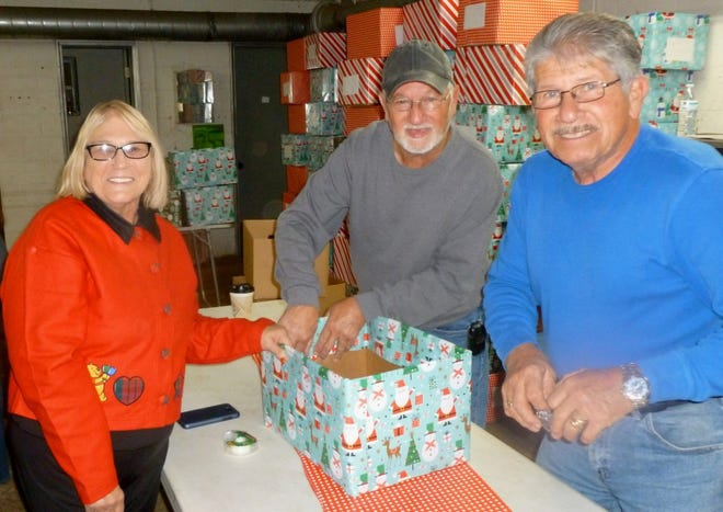 Civitan members (from left) Connie Kindley, Jerry Surratt and Harold Parrish wrap boxes with Christmas paper to then be filled with gifts to be distributed by Civitan Project Santa.