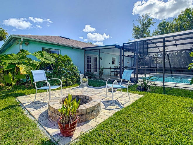 This Edgewater home's backyard – surrounded by a 6-foot privacy fence that was installed in 2017 – holds an inground pool, with a new extended, screened lanai, including updated electrical, and a patio area, with a firepit.