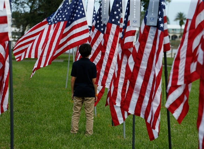 Volunteers set-up a Field of Honor display of 375 American flags with ribbons of a veterans name at New Smyrna Beach Riverside Park , Sunday, Nov. 1, 2020.