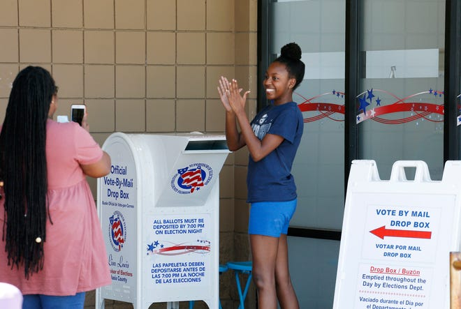 First time voter Tyja Davis celebrates after dropping her vote off in the drop box at the Supervisor of Elections office in DeLand, Monday, Nov. 2, 2020.