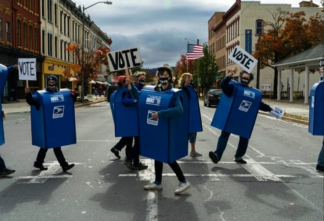 """Wayne County PA Democratic Committee posted photos on Facebook of this bunch wearing mailbox costumes, crossing Main Street, Honesdale, Oct. 24, urging people to vote by mail. They even danced to music by the Fred B. Miller Pavilion. The street theater production was called """"Delivering Democracy."""""""