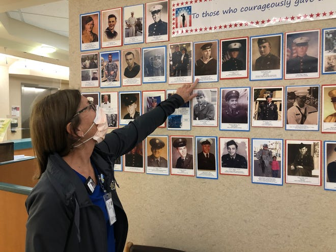 Ann MacDougall points out her dad on the Honor Wall at Noyes Health.