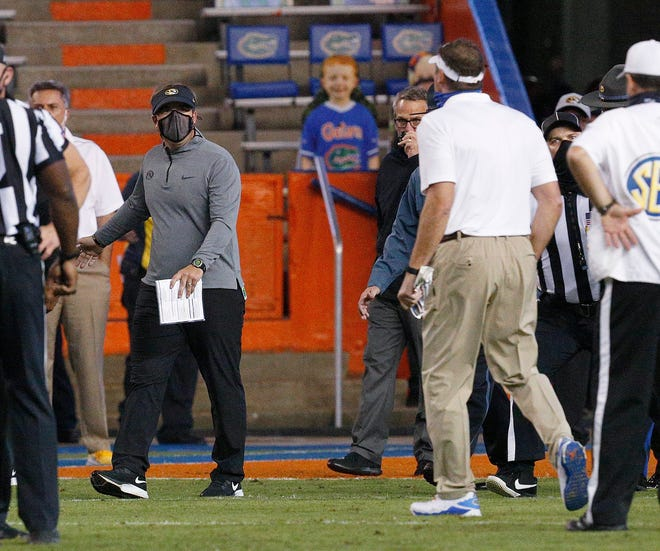 Missouri coach Eliah Drinkwitz, left, and Florida coach Dan Mullen, right, yell at each other after a fight broke out at the end of the first half of Saturday's game in Gainesville, Fla.