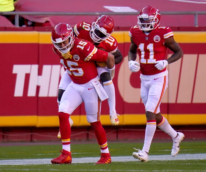 Kansas City Chiefs quarterback Patrick Mahomes (15) gives wide receiver Tyreek Hill (10) a ride on his back to the bench as wide receiver Demarcus Robinson (11) looks on following Hill's touchdown catch in the second half of Sunday's game against the New York Jets at Arrowhead Stadium.