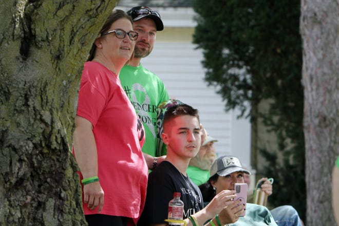 Spencer Weir, 14, surrounded by family members watches as vehicles go by during a drive-by Welcome Back parade for Spencer Weir, Saturday Aug. 29, 2020 outside his Burlington home. Weir, was severely injured with the bicycle he was riding was stuck head on by a vehicle in June. He has spent the last several months a rehabilitation facility in Nebraska.