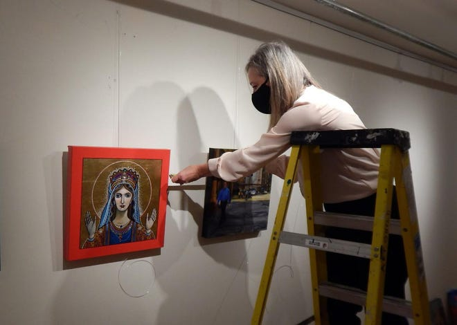 """Art Center of Burlington director Tammy McCoy hangs one of 24 original paintings Monday featured in the """"Artists of Fairfield & SE Iowa"""" show."""