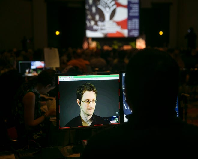 A video technician monitors a computer screen as National Security Agency leaker Edward Snowden appears on a live video feed broadcast from Moscow at a February 2015 event sponsored by the ACLU Hawaii in Honolulu. Former U.S. security contractor Edward Snowden says he will apply for Russian citizenship but not renounce his U.S. citizenship. The former contractor for the National Security Agency has been living in Russia since 2013 to escape prosecution in the U.S. after leaking classified documents detailing government surveillance programs.