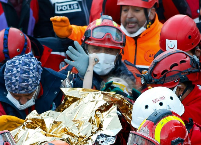Members of various rescue services carry 3-year-old girl Elif Perincek, after she was rescued from the rubble of a building, some 65 hours after a magnitude 6.6 earthquake in Izmir, Turkey, on Monday.