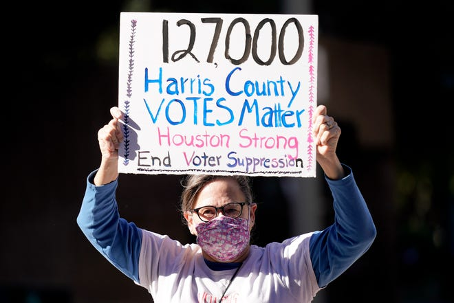Demonstrator Gina Dusterhoft holds up a sign as she walks to join others standing across the street from the federal courthouse in Houston on Monday, before a hearing in federal court involving drive-thru ballots cast in Harris County. The lawsuit was brought by conservative Texas activists, who have railed against expanded voting access in Harris County, in an effort to invalidate nearly 127,000 votes in Houston because the ballots were cast at drive-thru polling centers established during the pandemic.