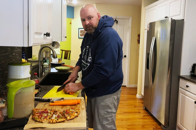 Kevin Fitzpatrick, an emergency room nurse at Hurley Medical Center in Flint, Mich., prepares dinner after his shift Thursday. Fitzpatrick said some nurses have quit in recent weeks even as the coronavirus resurges, putting more strain on remaining nurses.