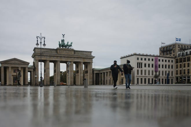 Two men with face masks cross the deserted Pariser Platz in front of the Brandenburg Gate, a tourist highlight, in Berlin, Germany, on Monday.