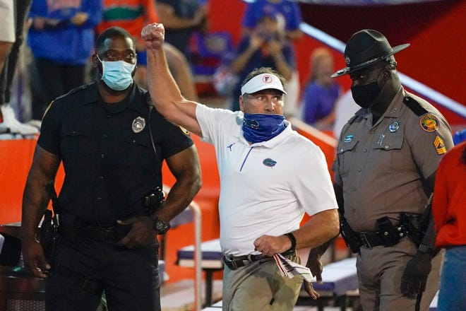 Florida head coach Dan Mullen, center, raises his fist to cheering Florida fans after an argument at the end of the first half as he was escorted to the locker room Saturday by law enforcement officers during the game against Missouri in Gainesville.