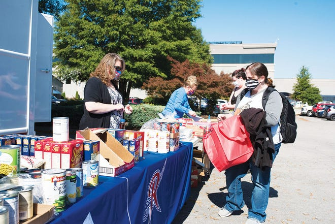 Roane State Community College Dean of Students Lisa Steffensen, left, and the college's student engagement coordinator Jennifer Fugate staff the farmer's market-style setup for the first 'Food Pantry On-the-Go' program.