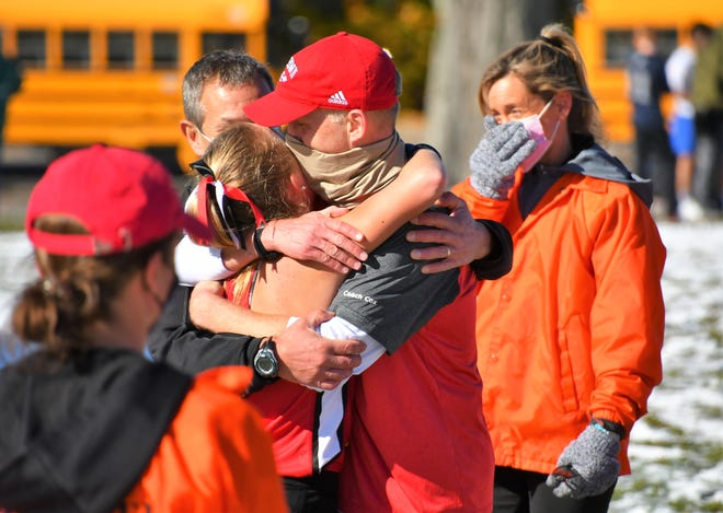 Coe-Brown co-coach Tim Cox hugs his daughter, Addison, after she won the girls Division II cross country championship Saturday in Manchester. Addison finished seventh in last year's meet while battling the effects of Lyme Disease.