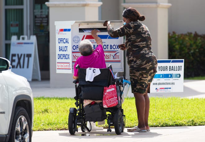 A woman helps a voter in a wheelchair get her ballot into the dropbox at the Supervisor of Elections office in West Palm Beach on Oct. 30, 2020. The Florida voting bill passed last week puts new restrictions on dropboxes and vote-by-mail ballots.