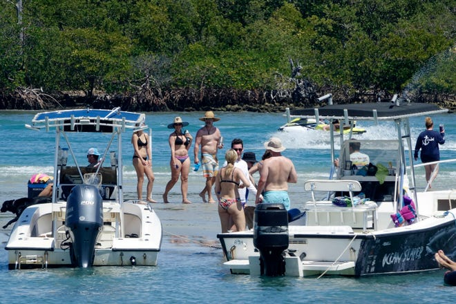 Boaters collect to socialize on the Tequesta sandbar on a sunny afternoon. Remember the pleasures of the before times, but don't let the memories trigger risky choices now.