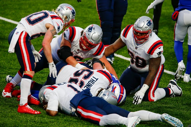 Patriots lineman Joe Thuney (62) fights for control of the ball after Cam Newton (1) fumbled late in Sunday's game against the Bills in Orchard Park, N.Y. The Bills won 24-21. Thuney is one of those players mentioned in a possible trade. [AP / John Munson]